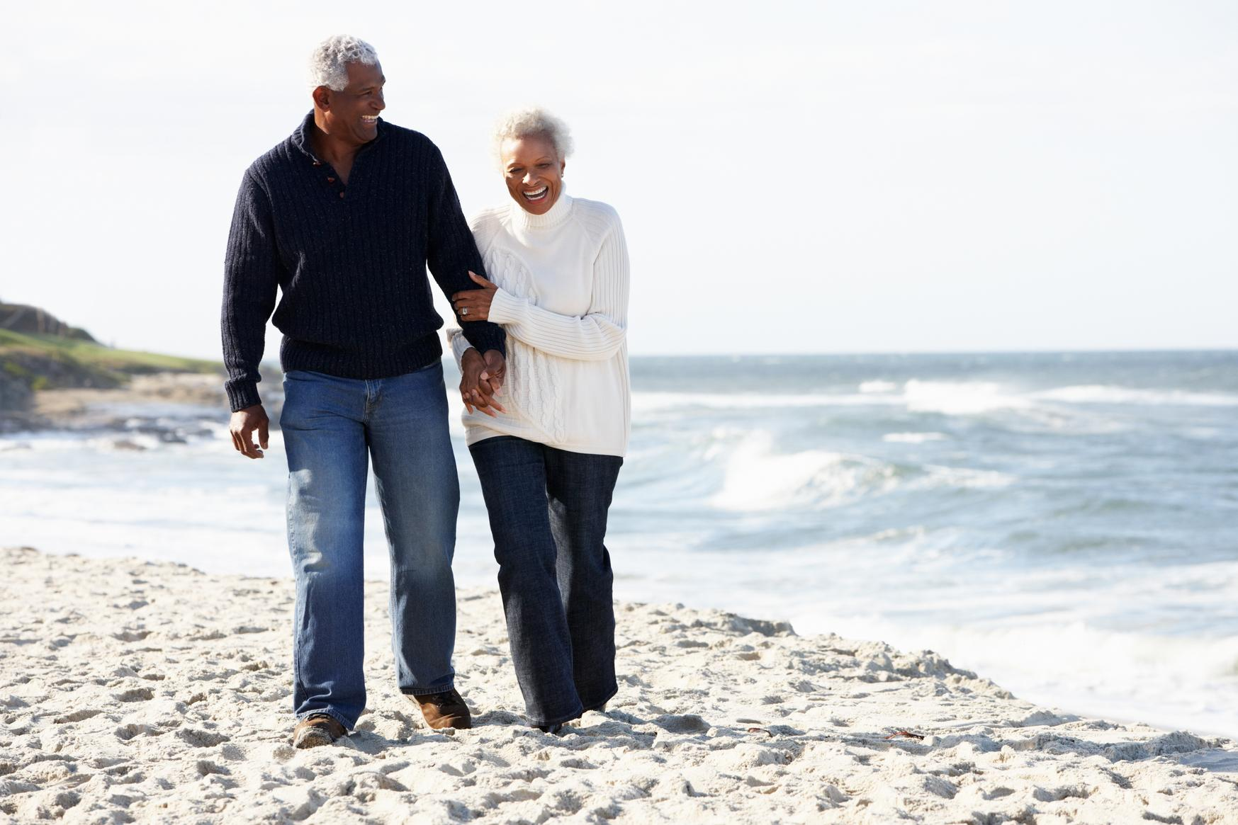 Senior couple walking along the beach together